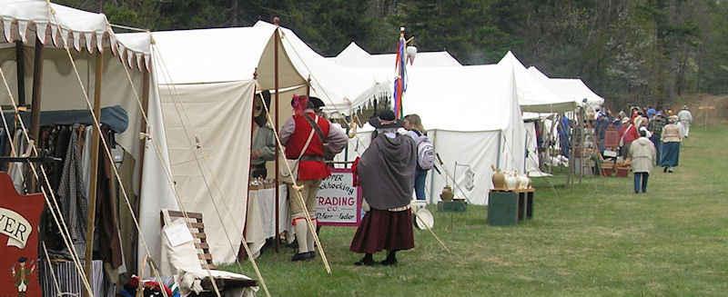 line of tents with individuals in 18th century wardrobe